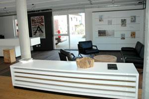 Der Gesprächsbereich: Die weiß lackierte Theke und das Bord bilden den Kontrast zum Parkett und den Holzobjekten, die das Material in seiner ursprünglichen Kraft zeigen. Parkett ist vielfältig einsetzbar, sogar in der Malerei, wie das Acylbild eindrucksvoll beweist