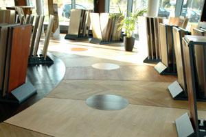 Die Parkett-Ausstellung: Vom schmalen Stab- über Massivparkett und Langholzdielen bis hin zum Tafelparkett ist alles da und flächig verlegt. Auf den Musterflächen stehen Ständer mit den dazugehörigen Holzarten.